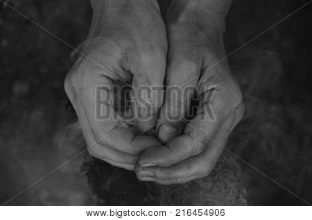 Hands clasped together. Adult man smoke log background.