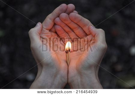 Burning matches in hands. The flame from the matches pointing to the up. Adult man dark forest background.