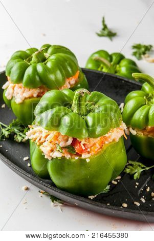 Autumn recipes. Home stuffed bell pepper with minced meat carrots tomatoes herbs cheese. Cooking process. White marble table. Stuffed pepper ready for baking in pan Copy space