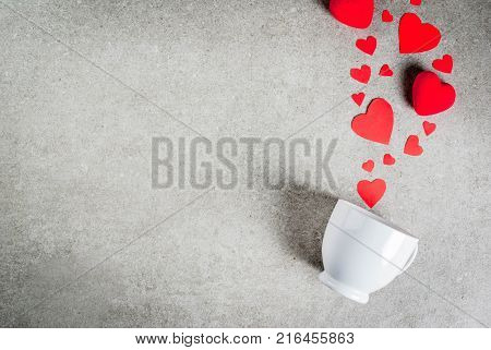 Romantic background Valentine's day. A gray stone table with a cup for coffee or hot chocolate decorated with paper and plush red hearts top view flat lay copy space