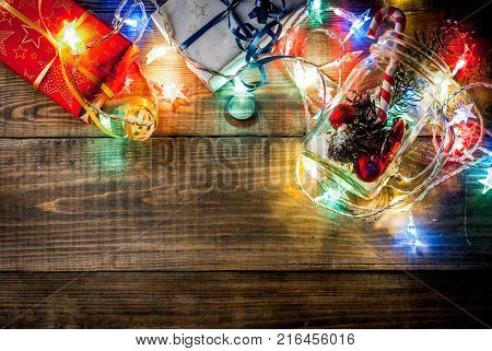 Christmas New Year's concept. Mason Jar with decorations fir cones artificial snow candy cane and fir branch. On a wooden table background with a lit garland turned on. Copy space top