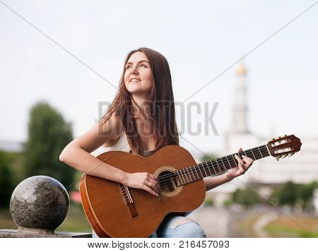 Guitar romantic city musician concept. woman playing stringed instrument. Lifestyle of talented people.