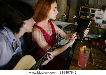 young people seeking helpful online information about how to play guitar. modern technology education benefits concept