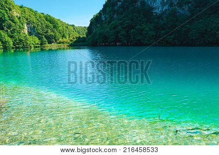 Plitvice Lakes National Park Croatia Europe. Natural park with waterfalls and turquoise water. UNESCO World Heritage site. Blue clear water of Plitvicka Jezera. View of lake hills. Summer landscape