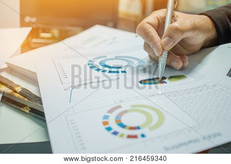 Businessman Preparing reports papers with graphs charts on Stacks of documents files for finance in office. Piles of unfinished document achieves with paper clip. Concept of Business Annual Report.