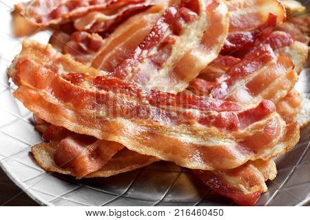 Cooked bacon rashers in pan, closeup