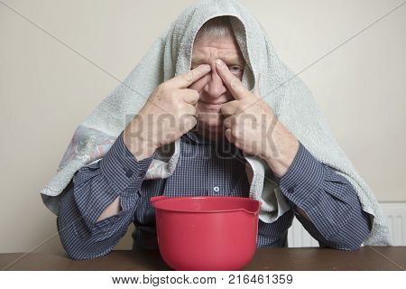 Mature man with a cold and sinus issues  inhaling steam with a towel over his head