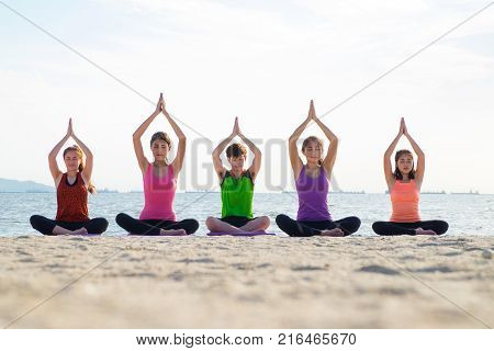 Yoga class at sea beach in evening ,Group of people doing tree poses with clam relax emotion at beach,Meditation pose,Wellness and Healthy balance lifestyle