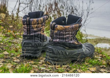 A pair of worn hiking boots on natural background. Dirty boots for hiking fishing traveling.