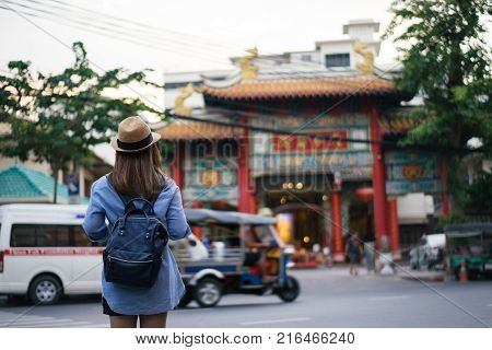 Young asian woman traveler with blue backpack and hipster hat looking view of Chinese temple with tuk tuk Thailand background at China Town Bangkok. Traveling in Bangkok Thailand