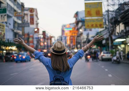 Young asian woman traveler with blue backpack and hipster hat looking night view on road with tuk tuk Thailand background at China Town Bangkok. Traveling in Bangkok Thailand