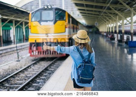 Young woman traveler with sky blue backpack and hat looking the map with train background at train station Bangkok. Traveling in Bangkok Thailand. Travel concept
