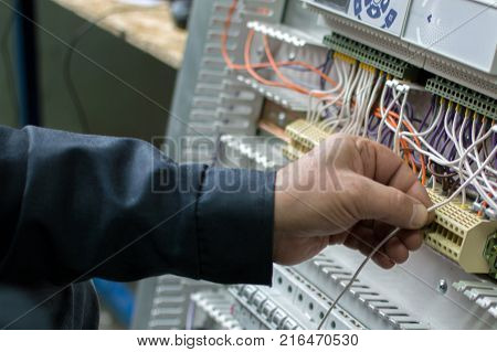 Electrician Assembling Industrial Hvac Control Cubicle In Workshop. Close-up Photo.