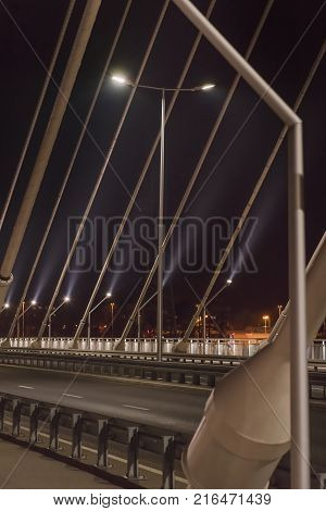 sidewalk and highway going through a cable-stayed bridge with big steel cables, closeup at night time in bright lights