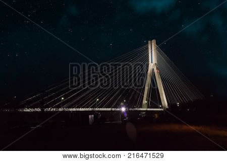Cable-stayed bridge close-up at night against the background of the starry sky and clouds