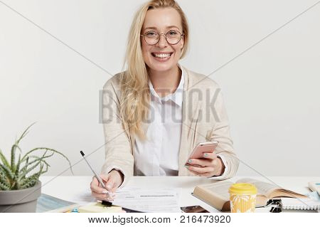 Indoor Shot Of Successful Young Businesswoman Has Appealing Appearance Looks With Smile, Writes Info