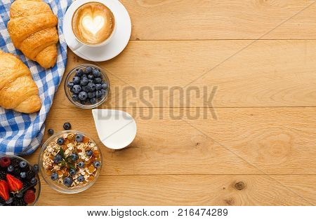 Rich continental breakfast. French crusty croissants, muesli, lots of sweet berries, hot coffee for morning meals. Delicious start of the day. Top view with copy space on wooden table