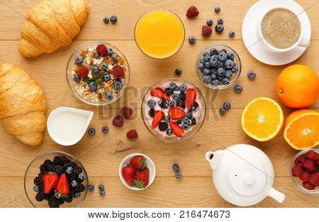 Rich continental breakfast. French crusty croissants, muesli, yogurt, milk jar, tea pot, cup of hot black coffee and lots of sweet berries for tasty morning meals. Delicious start of the day, top view