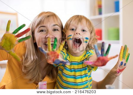 Cheerful child boy and his mother having fun and showing hands painted in colorful paints