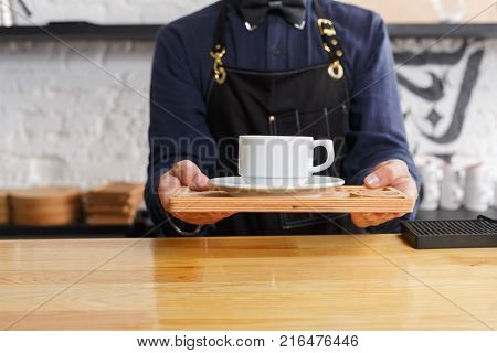 Unrecognizable barman welcoming guests at coffee house counter. Portrait of male bartender in uniform offering hot coffee cup. Small business, occupation people and service concept, copy space