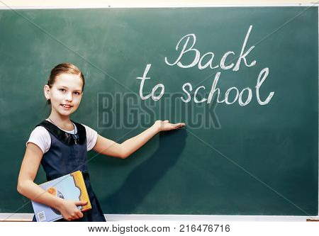 Happy child near the board with the inscription back to school