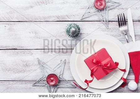 Christmas table setting. Gift box fir tree white plate and silverware on rustic table top view. Preparation for holiday dinner.