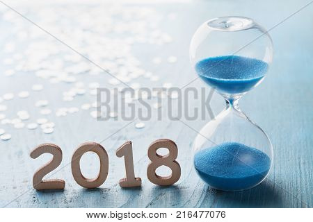 New year 2018 greeting card. Hourglass or sandglass on blue wooden table.