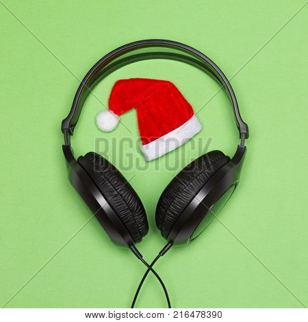 Headphones and Santa hat. Christmas songs minimal concept