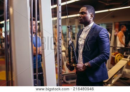 Handsome african man with big muscles in classic suit, posing at the camera in the gym. fitness center