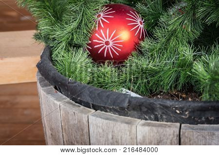 close up image of a bright red Christmas ball nestled in green Christmas fern planted in an old wood rustic bucket.
