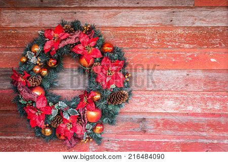 green Christmas wreath decorated with red poinsettia hanging on one side of a red rustic board background great idea for Christmas card.