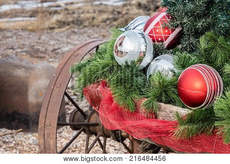 close up image of Christmas ball ornaments lying on an old rustic wagon with rusty wheel