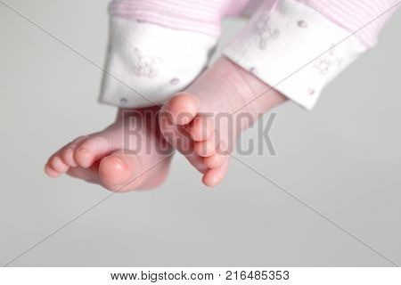 A baby's feet exposed. Light pink and white trousers. Baby girl. Light gray background.