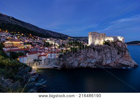 View of Fort Lovrijenac (St. Lawrence Fortress) on top of a steep cliff and the city of Dubrovnik in Croatia at dark.