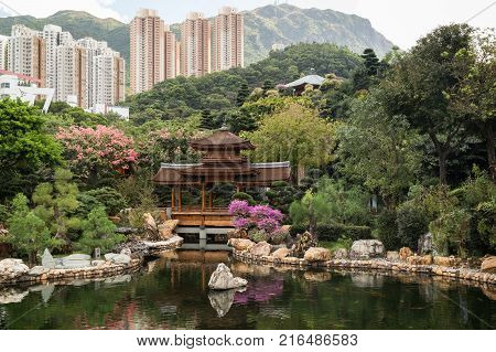 Traditional wooden bridge by the pond at the Nan Lian Garden in Hong Kong, China. High-rise apartment buildings in the background.