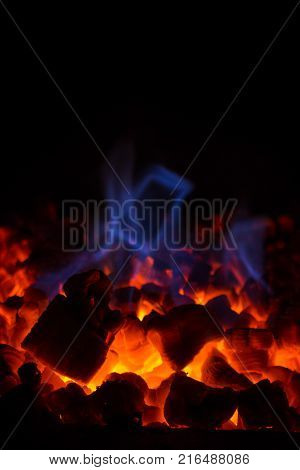 Close-up of glowing hot red embers (coal) and blue flame in a fireplace