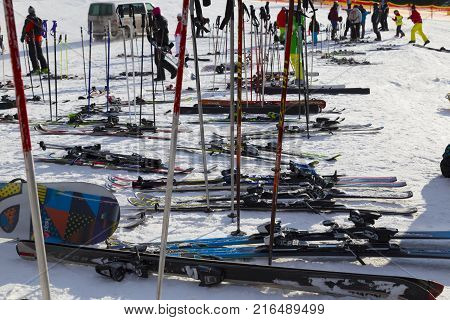 Jasna Demanovska valley Low Tatras Slovakia January 19 2016 : Famous ski resort. Alpine skis and poles lie on snow-covered slopes. People in sport ski clothing. Parents and children spend time together. Concept winter holiday active healthy lifestyle
