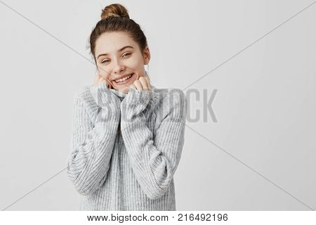 Headshot of adorable smiling woman wrapping up her face in collar of grey sweater. Female artist expressing appeasement and comfort. Feelings concept