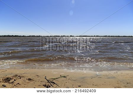 Panoramic view of Rio Parana. A morning on the beach in Rosario, Santa Fe, Argentina.  The sun is reflected on the water.