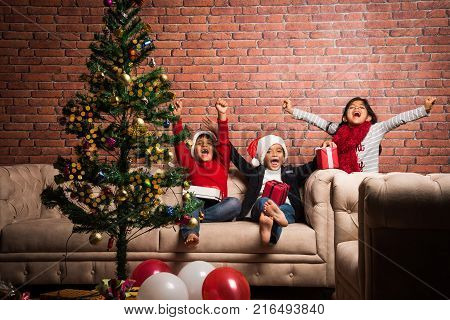 Indian kids celebrating christmas - cute little Indian kids playing, laughing and having fun with gift boxes on christmas, sitting on floor or sofa with christmas tree in the background