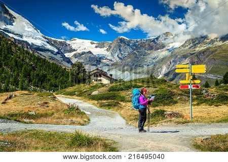 Stunning alpine landscape, hiker woman with backpack, paper map, orientate and find direction in high mountains, Zermatt, Valais region, Switzerland, Europe