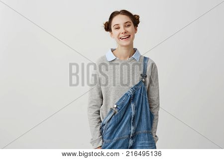 Cheerful woman being in good mood laughing looking on camera over white wall. Happy emotions of carefree female smiling with teeth being contented. Positive human facial expressions