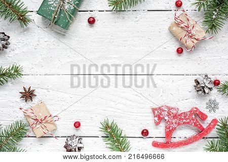 christmas composition. frame made of fir branches red berries retro christmas toy gift boxes and pine cones on white wooden table. Christmas background. Flat lay. top view with copy space
