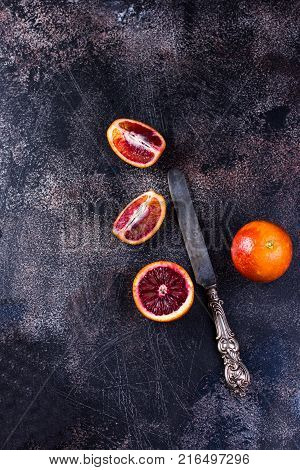 Whole and sliced sicilian oranges on a black slate background. High angle view