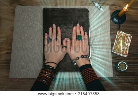 Book of magic. Tarot cards on fortune teller desk table. Future reading. Woman witch reads a ancient magic scroll book with copy space and learn art of prediction on wooden table.