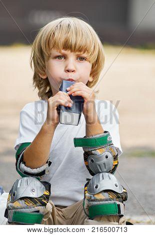 Portrait of little boy roller skater drinking juice