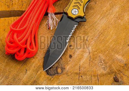 Black knife blade with a serritorial blade. Cut parachute cord.