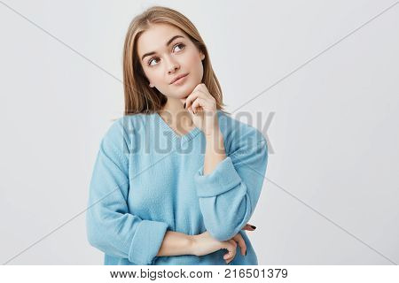 Human face expressions and emotions. Thoughtful young pretty girl in blue sweater holding hand under her head, having doubtful look while can't decide what clothes to wear on her friend's birthday party