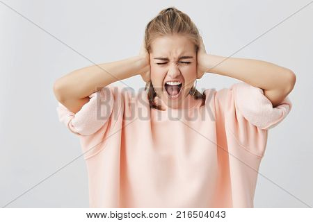 Shouting emotional in despair young caucasian woman, with open mouth and closed eyes, screaming, closing her ears as refusing to listen bad news. Face expression, reaction and negative emotions.