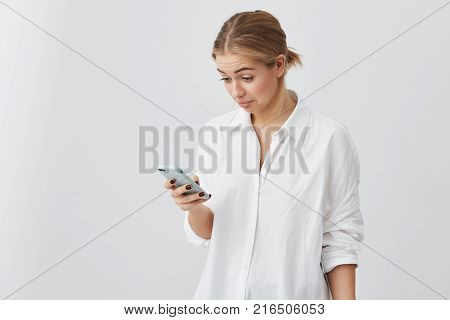 Pretty blonde girl looking with puzzled face expression at screen of her smartphone. Good-looking caucasian female wearing white shirt looking confused after reading message from her friend.